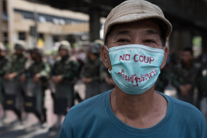 A protester stands in front of a line of soldiers in Bangkok while wearing a mask bearing the message 'No coup'. Photo by Atiwat Silpamethanont, Copyright @Demotix (5/25/2014)