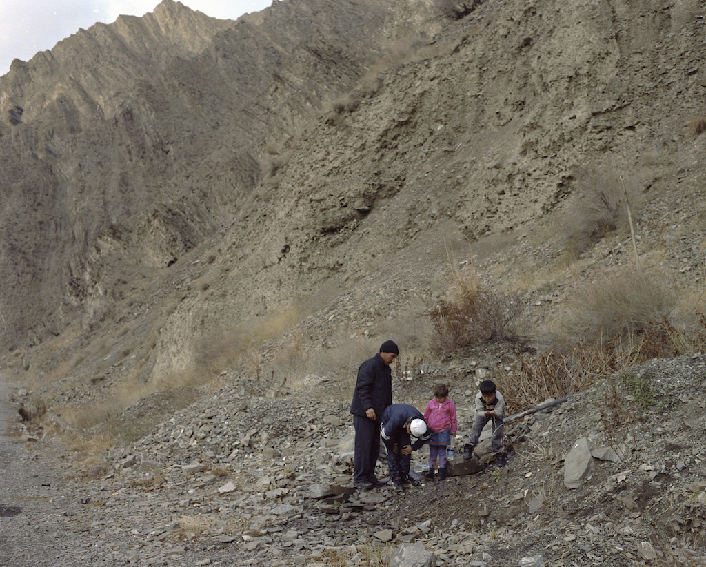 A family drinks water from a pipe jutting out of the mountains in the Naryn region of Kyrgyzstan. Photo by Fyodor Savintsev / Salt Images, 2013.