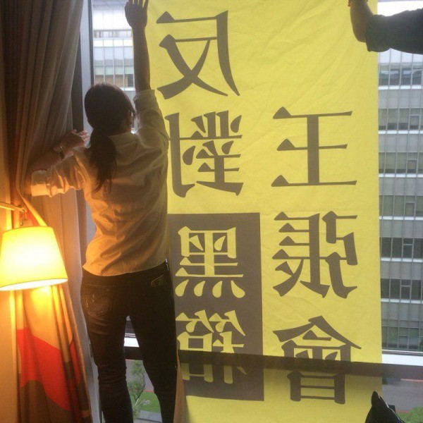 "The protest banner hanging on the hotel window said ""Against the black-box meeting between Wang and Zhang"". Photo from Democracy Tautin's Facebook page."