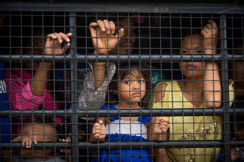 A Cambodian migrant family onboard a truck that will take them to the border where they will leave Thailand. Photo by Lee Craker, Copyright @Demotix (6/17/2014)