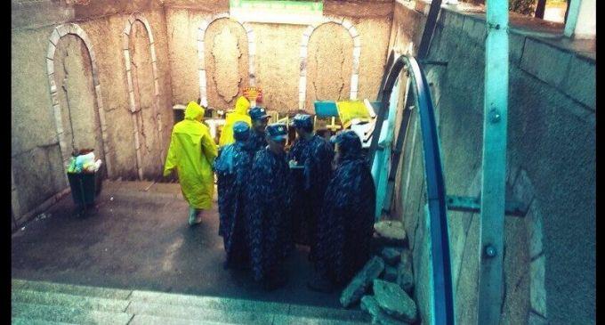 Police in raincoats take shelter in Almaty