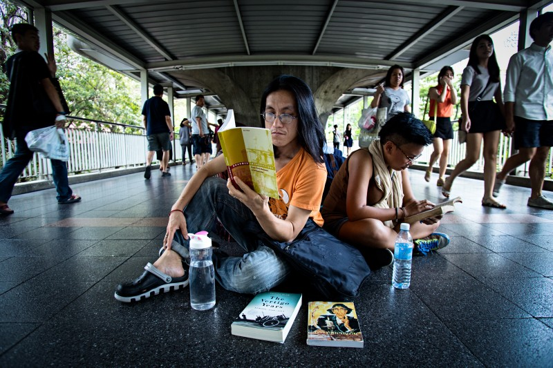Thai anti coup protesters continued to defy the military ban on gatherings by silently reading books in public places. Photo by Lillian Suwanrumpha, Copyright @Demotix (5/31/2014)