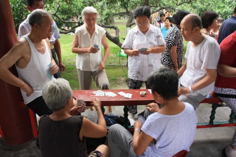 Retired seniors play cards in a park in China.