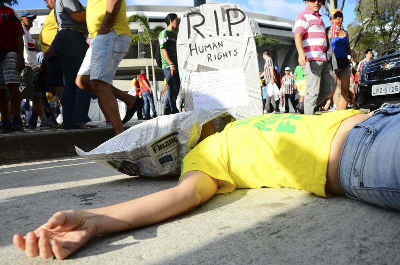 A young woman stages a lone protest against FIFA in front of the Maracana stadium after Belgium played Russia in their group stage match on June 22, 2014, despite a large security cordon designed to block such demonstrations against the 2014 World Cup. Photo by Marcelo Fonseca. Copyright Demotix.