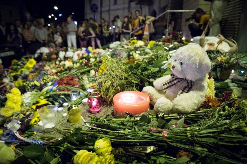 Ukrainians bring flowers, candles and toys to the entrance of the Dutch Embassy in Kiev on June 17, 2014. Malaysian Airlines airliner MH17 Amsterdam - Kuala Lumpur was shot down earlier in the day. Photo by Oleksandr Ratushniak. Copyright Demotix