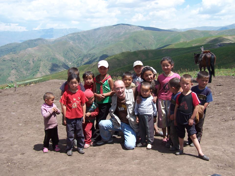 Igor Rotar, a former correspondent for Nezavisimaya Gazeta, has worked extensively in Central Asia. Here he poses with children in Kyrgyzstan. Photo taken from Rotar's Facebook. Used with permission.