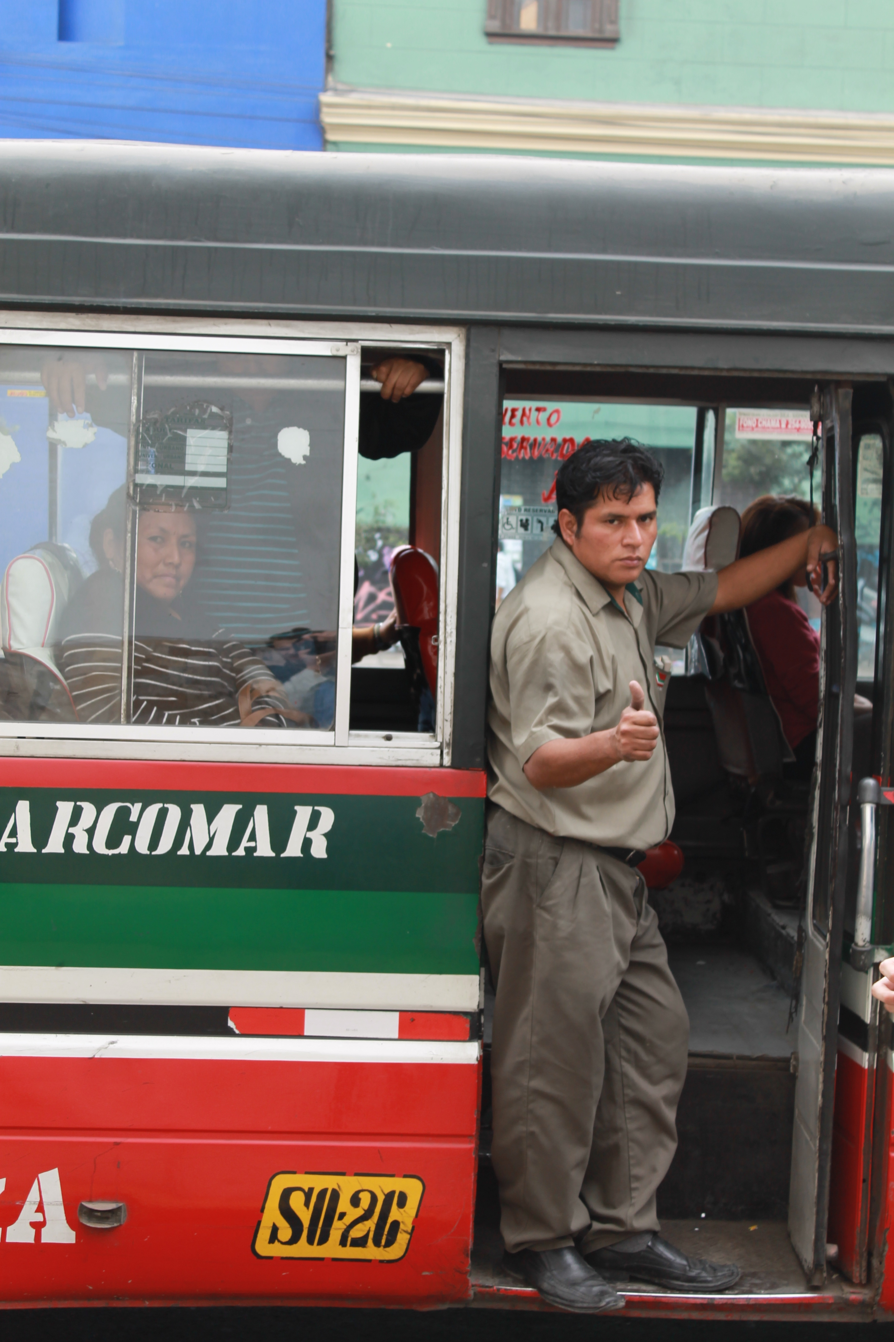 """A conductor on one of Lima's combis, private minibuses which compete with Lima's taxis for both passengers and road space. Officials want to reduce their number, saying they cause accidents and are poorly maintained. Photo by Alex Pashley."