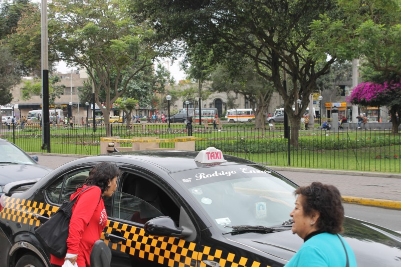 A passenger interacts with the driver of a Lima taxi sporting the new regulation black-and-yellow stripes and lighted sign. Some Lima residents say marking licensed taxis in this way will make them feel safer. Photo by Alex Pashley.