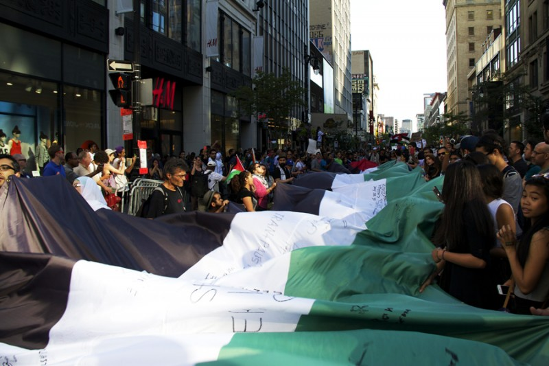 """Montreal protesters holding the longest Palestinian flag in the world during Gaza Solidarity protest on Friday July 11, 2014."""