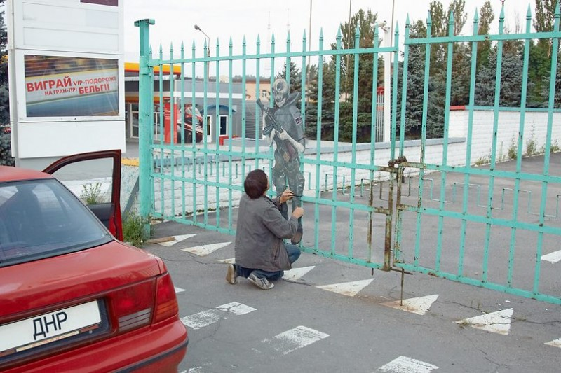 Zakharov himself, attaching a new artwork to a fence in Donetsk. Image from Facebook.