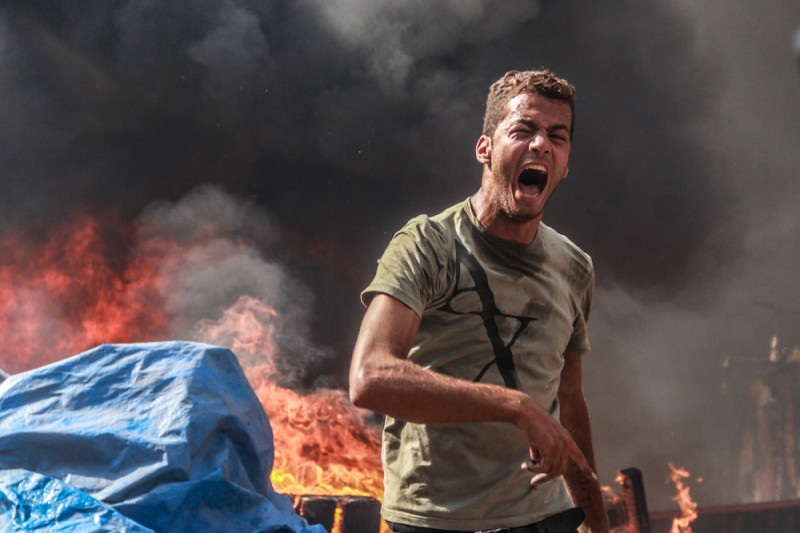 A young Egyptian flees from the horror of the Rabaa Massacre. By Mosa'ab Elshamy. From his Flickr Account. Taken on August 14, 2013. Used with Permission.