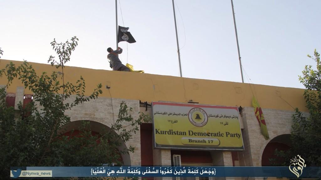 Militant hoisting the Islamic State flag, replacing the Kurdish flag