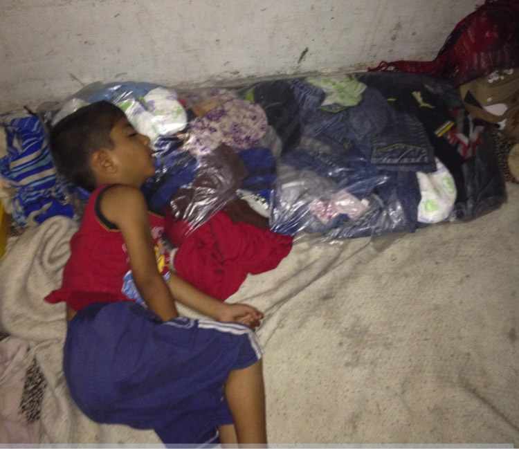 A child sleeping on a make-shift pillow made of a bag of clothes in Heba's room. Photo by author.
