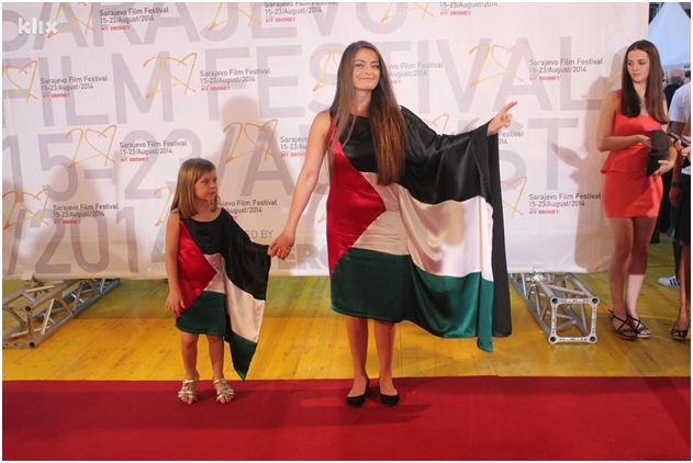 "Sabina Šabić and her daughter, Sara, in the ""flag gowns"" at the Sarajevo Film Festival red carpet, August 2014. Photo by Davorin Sekulić/klix.ba, courtesy of Media Centar Sarajevo, used with permission."