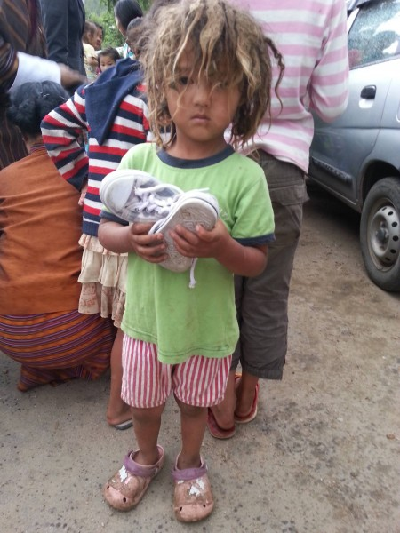 A little girl with a pair of recycled shoes during distribution in Ghasa. Image used with permission.