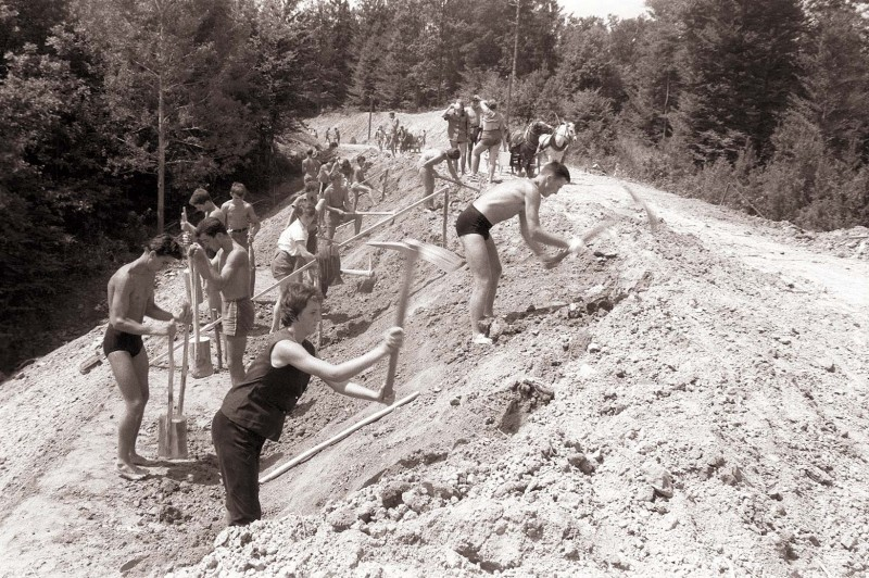 Volunteers reconstructing a country road in Slovenia during a youth work action in 1960. This image is public domain.