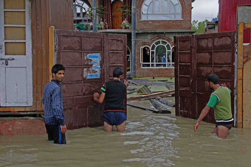 A group of youth try to evacuate goods from a flooded house in Bemina Srinagar, Kashmir. Image by Faisal Khan. Copyright Demotix (5/9/2014)