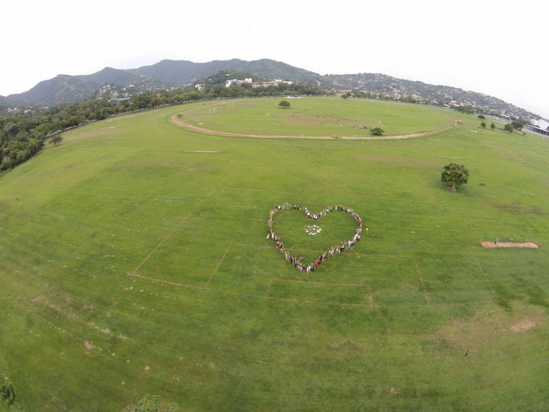 Participants of the climate change march in Trinidad and Tobago form the shape of a heart in the Queen's Park Savannah in Port of Spain. Photo by Nico Kersting, courtesy IAMovement, used with permission.