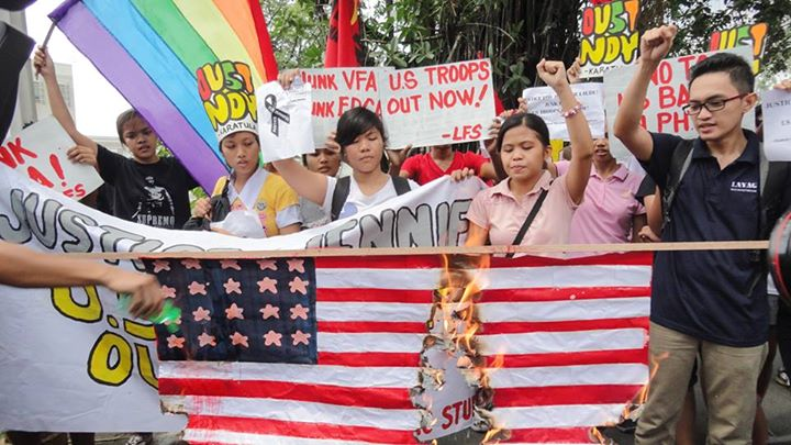 Activists burn a US flag during a protest action in front of the US Embassy. Photo Credits: Richard James Mendoza.