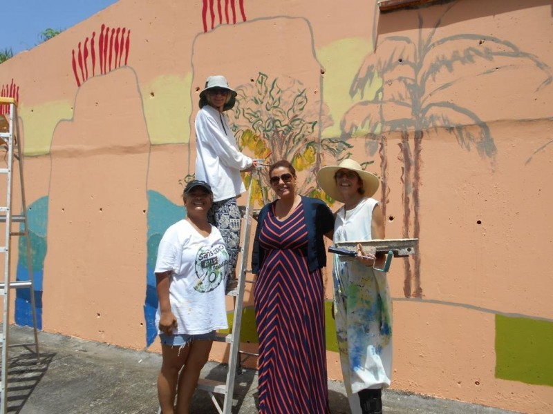 "Grenada's Minister of Tourism, Civil Aviation and Culture, the Hon. Alexandra Otway-Noel, visits some of the artists working on the ""Paradise Lost"" mural - Suelin Low Chow Tung, Xandra Shaw and Victoria Slinger. Photo courtesy the artists; used with permission."