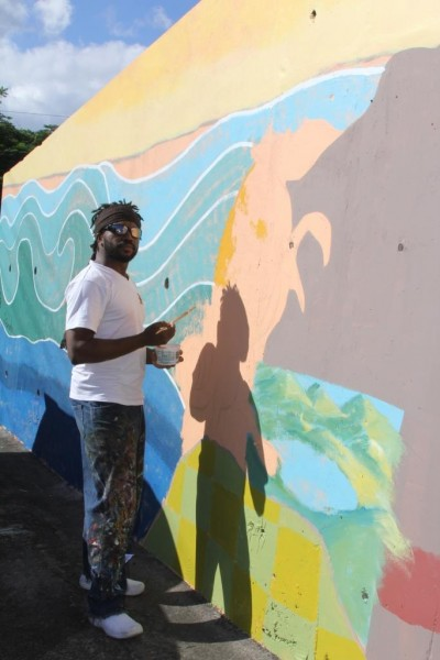Haitian artist, Prensnelo, paints the armadillo of the Grenada climate change mural. Photo courtesy the artists; used with permission.