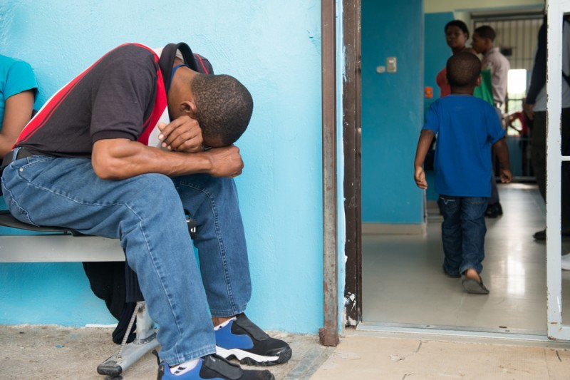 A man from the Dominican Republic bows his head as a child walks into a hospital for treatment. The disease has spread quickly Caribbean-wide. Photo courtesy the Pan American Health Organisation, used under a CC BY-ND 2.0 license.