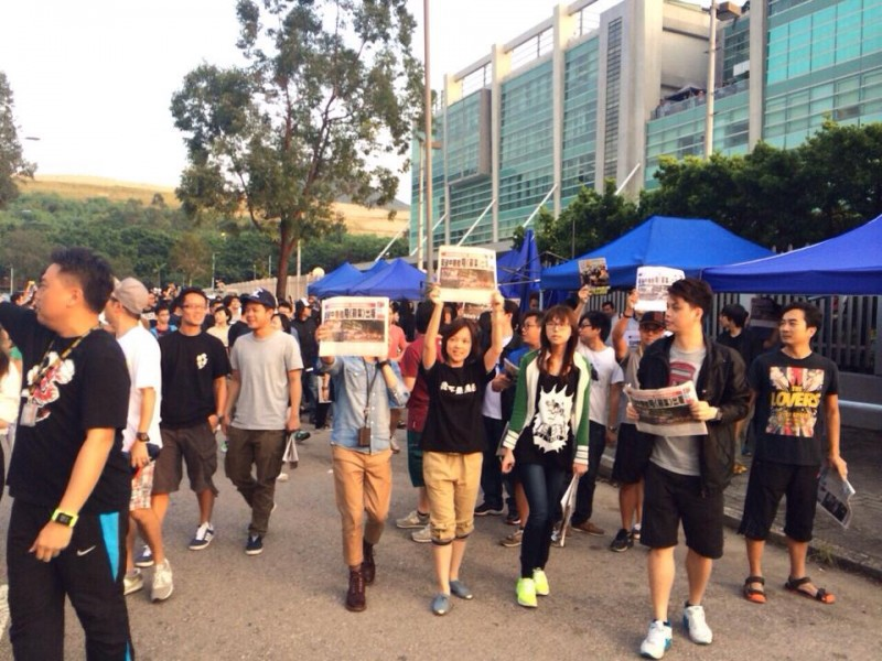 Staffs from Apple Daily confronted with the mobs outside the media outlet's headquarter by holding up the newspapers. Photo from Chan Pui Man's Facebook.