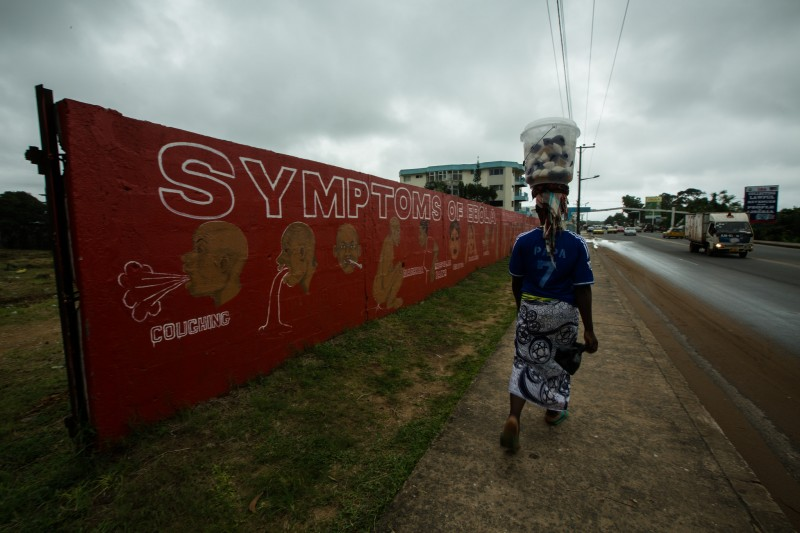 A resident walks past a mural about the dangers of the Ebola Virus painted on a wall off Tubman Boulevard in Monrovia, Liberia. September 18, 2014. Photo by United Nations Development Programme on Flickr. CC BY-NC-ND 2.0