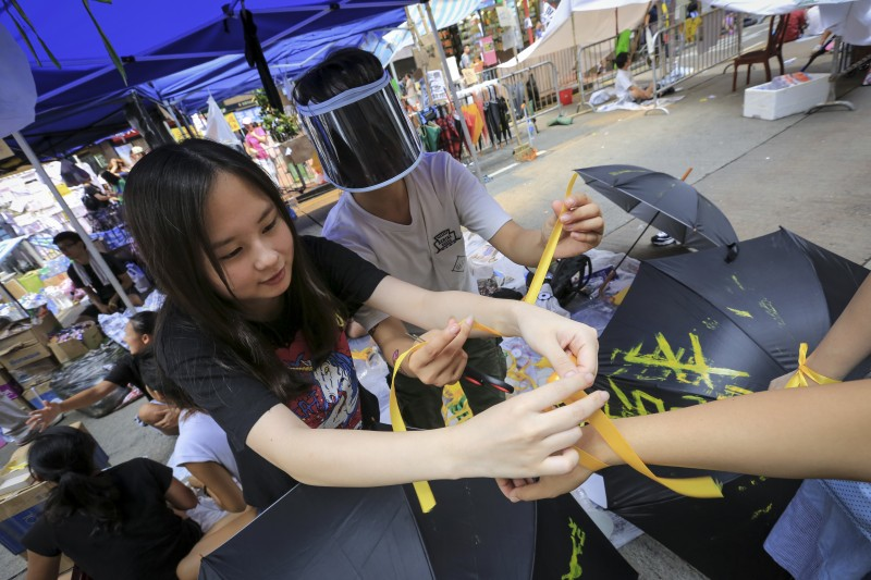 Protesters tie yellow ribbons to the arms of those who wish during the Hong Kong protest in Causeway Bay on October 1, 2014. Photo by Guillaume PAYEN. Copyright Demotix