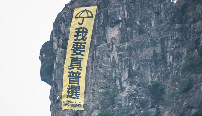 "A group of mountain climbers hang a huge banner, ""I want genuine universal suffrage"" in Lion Rock, one of the most well-known landscape in Hong Kong.  The group explained their action to local media: ""We were shock[ed] by CY Leung's viewpoint that the poor should not have equality in election[s] and hope this action would be able to call public attention on the importance of universal suffrage."" Image from Hong Wrong."