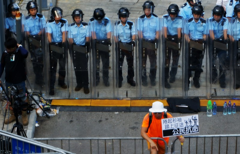 A protester holds a sign of 'civil disobedience' in front of a line up of riot police on September 27, 2014 as part of Occupy Central protest outside government headquarters at Admiralty, Hong Kong. Photo by P H Yang. Copyright Demotix