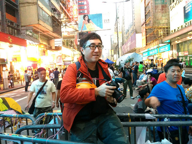 "After the interview, Rayman went in the front of the road barricade in Mongkok's protest site, put on his yellow helmet with a ""press"" sticker on it, and started his photo shooting for the evening. Photo taken by Ip Iam-Chong inmediahk.net."