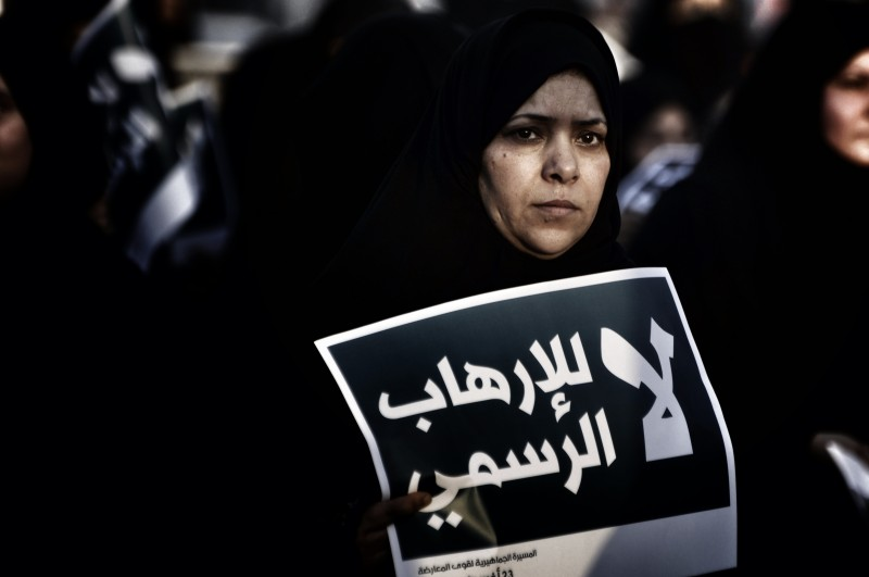 "A protester in Bahrain holds a sign that reads: ""No to the state-sponsored terrorism, Bahrain is a gulf state that is witnessing the third year of an uprising led by the majority Shia population. Photograph by Hussain Altareef. Copyright: Demotix"