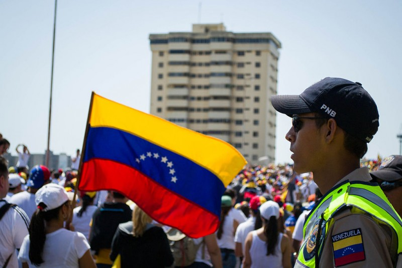 A police officer watches protesters in Maracaibo, Venezuela 2014. Photo by María Alejandra Mora via Wikimedia (CC BY-SA 3.0)