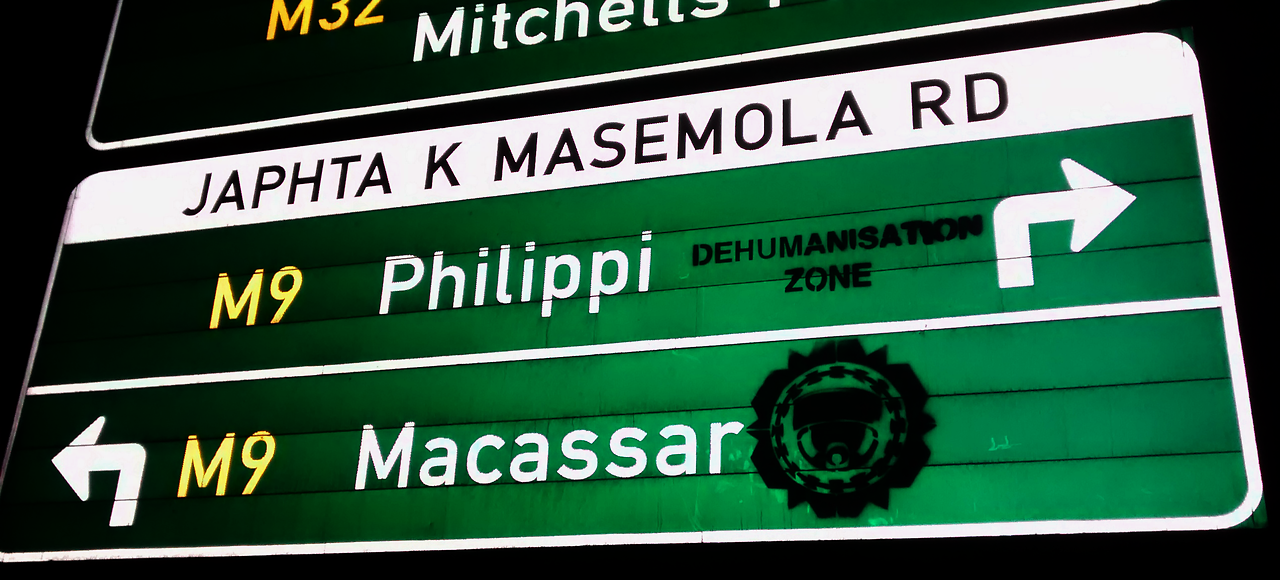 A traffic sign showing how to get to Khayelitsha, a 'dehumanisation zone'. Image source: http://tokolosstencils.tumblr.com/.