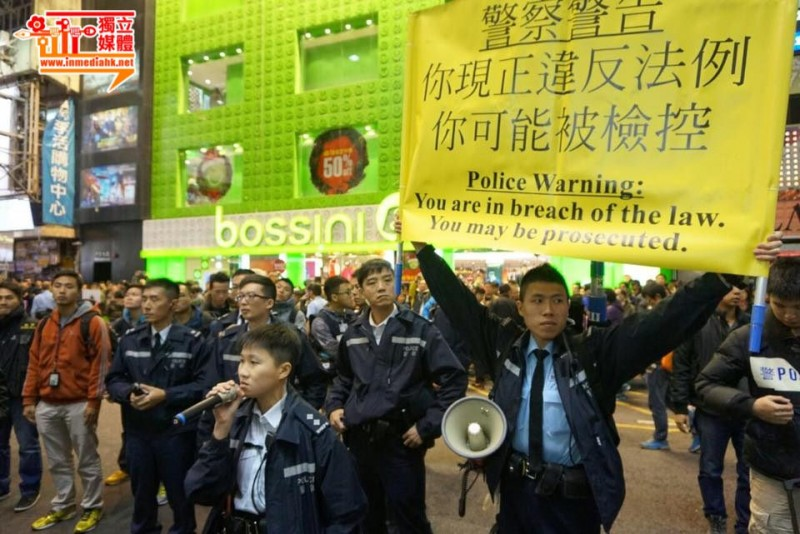Police officers raised a yellow flag in Mong Kok shopping district before they took arrest action.