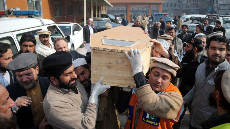 Men carry the casket of a victim of the Taliban shoot-out in a military-run school in Peshawar, Pakistan. Image by ppiimages. Copyright Demotix (16/12/2014)
