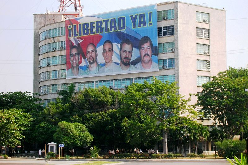"A Havana billboard depicting the faces of the five jailed Cubans reads, ""Freedom Now!"" Photo by Giorgiopilato via Wikimedia Commons. Released to public domain."