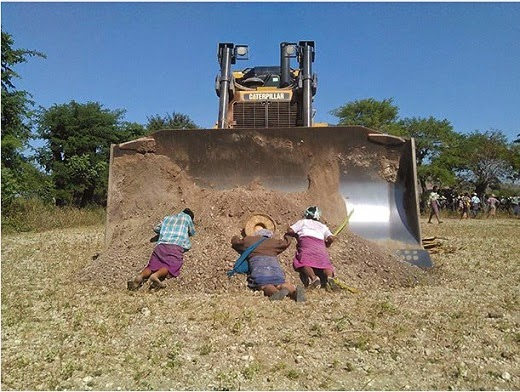 Farmers lie in front of a bulldozer to protest the fencing of their land by a copper mining firm. Photo by Han Win Aung, The Irrawaddy Blog