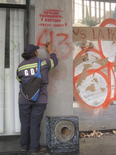 "A Mexico City's government employee tries to clean graffiti of the number ""43"" off a municipal. building. T ""43"", representing the number of students who were ""disappeared"" from their school in Ayotzinapa in September, has  become a symbol of protest for many Mexicans.  Photo by Robert Valencia."