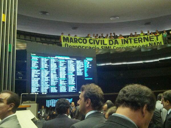 A screen shows the vote tally as activists cheer for the bill from the upper level of the Chamber. March 2014. Photo shared by Carolina Rossini via Twitter.