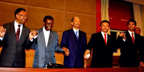 Madagascar president with 4 of his predecessors holding hands at a national unity meeting - Public domain