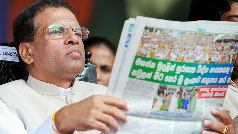 Sri Lanka's main opposition presidential candidate Maithripala Sirisena reads a newspaper during a campaign rally for the upcoming presidential elections in Colombo. Image by Chamila Karunarathne. Copyright Demotix (31/12/2014)