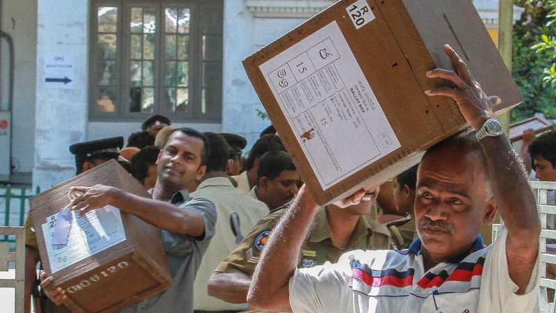 Sri Lankan election commission workers carry ballot boxes while escorted by police on the eve of presidential elections in Colombo. Image by Chamila KarunaRathne. Copyright Demotix (7/1/2015)