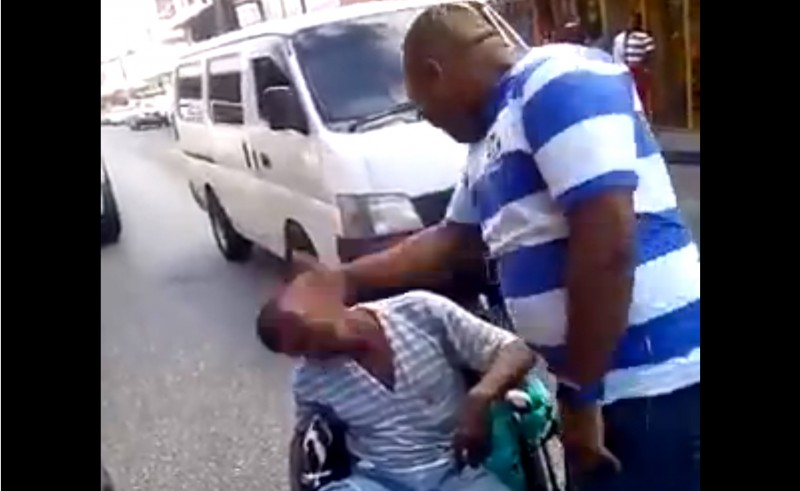 A screenshot of the video that has been circulating on social media showing a plain-clothes policeman in Trinidad and Tobago slapping a man in a wheelchair.