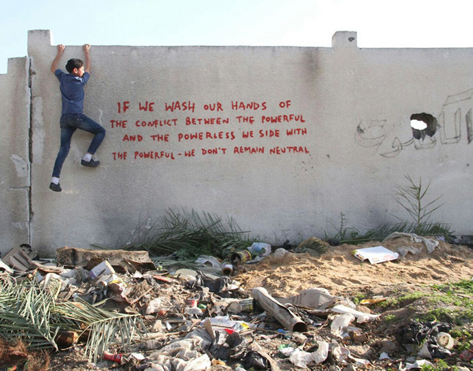 Palestinian kid climbs the wall featuring Banksy's message
