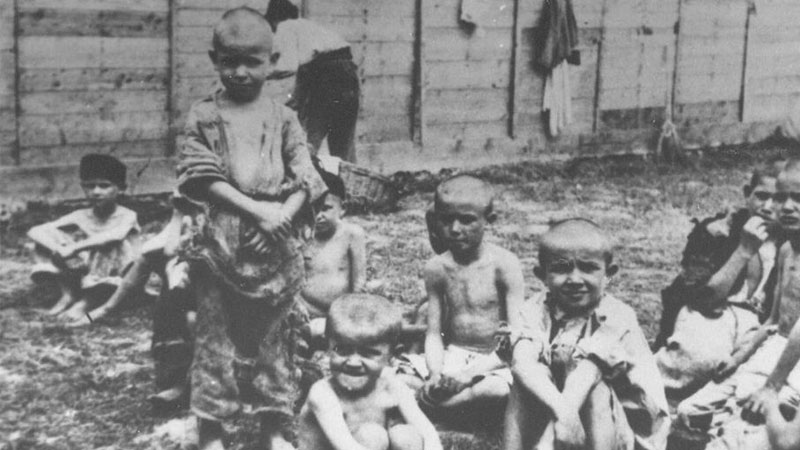 Children sitting in front of one of the barrack's in the Sisak concentration camp. Public domain.