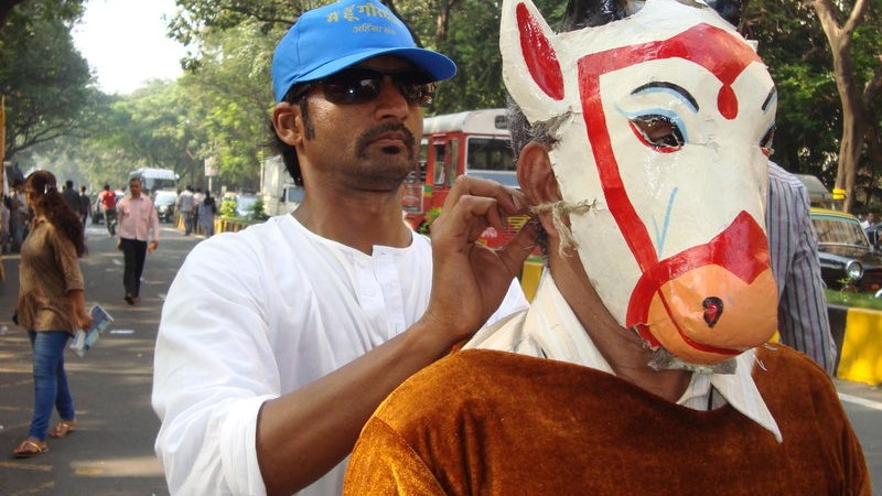 An activist ties a mask of a cow on another, demanding banning of cattle slaughter.