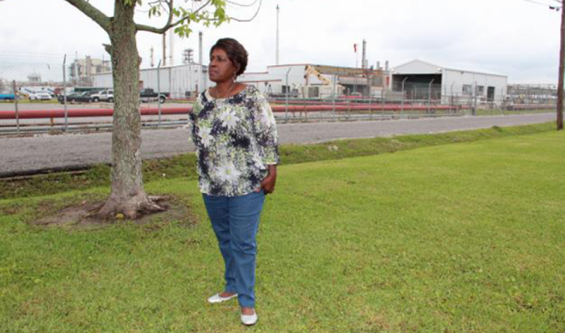 Margie Richard stands in what used to be her front yard, across the street from Shell's chemical plant in Norco, Louisiana. Richard pushed for the company to buy out the neighborhood and move residents. Credit: Reid Frazier. Published with PRI's permission.