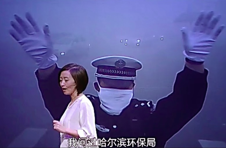 Chai addresses her audience with a picture from the smog-filled Northeastern city of Harbin in the background.